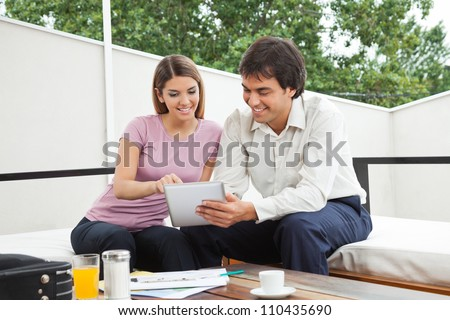 Indian male architect having discussion with female client over a digital tablet