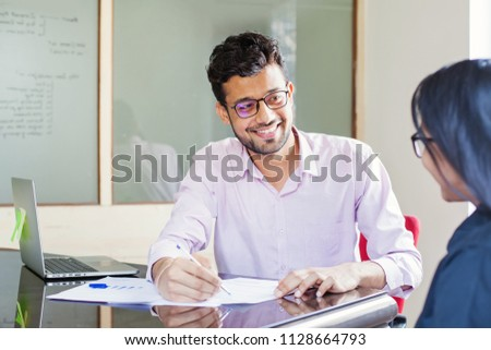 Indian man explaining contract to a colleague
