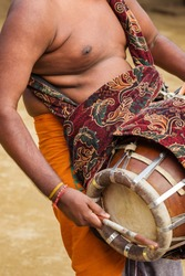 Indian man playing drum during temple festival in Kerala, India