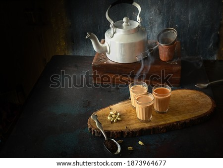 indian masala chai or tea ion ttraditional glasses, with kettle, spices and tea leaves on dark, wooden background. cafe, retro, restaurant, hotel concepts.