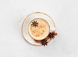 Indian Masala chai tea. Traditional Indian hot drink with milk and spices on white concrete background. Top view, flat lay.