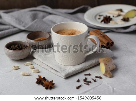 Indian masala chai, traditional spiced  black tea with milk in white cup and spice ingredients on grey background