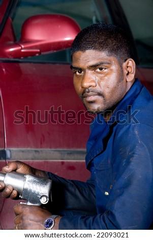 indian mechanic changing vehicle tyre