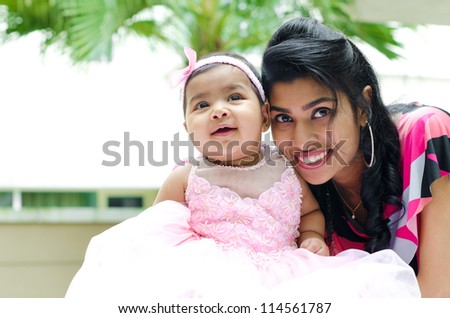Indian mother and baby girl at outdoor home garden