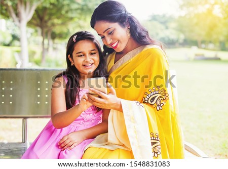 Indian mother and daughter in traditional ethnic clothes using mobile phone on a bench of the park in Delhi
