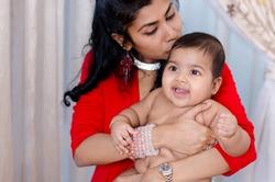 Indian mother kissing her baby girl, indoor
