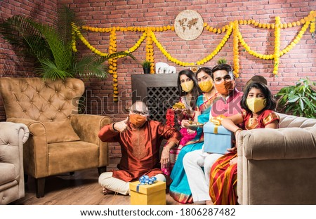 Indian multi generation Family wearing protective medical face mask during festival in coronavirus and flu outbreak. Virus and illness protection, quarantine. COVID-2019