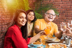 Indian multigenerational Family eating food at dining table at home or restaurant. South Asian grandfather, mother, father and two daughters having meal together