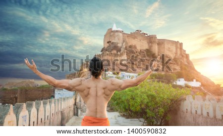 Indian muscled fit male model posing in pride outdoor showing his back muscles with mehrangarh fort of jodhpur in background - Image
