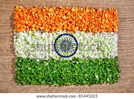 Indian national flag from chopped raw vegetables: carrot, cabbage and green beans on the textured table represent pure vegetarian cuisine