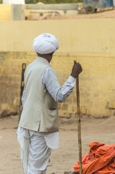 Indian old village farmer with white turban and stick in hand