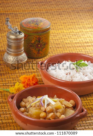 Indian or Thai chickpea and potato curry in an earthenware dish with a separate dish of white basmati rice.  On a bamboo mat with oriental pepper pot and spice container. - stock photo