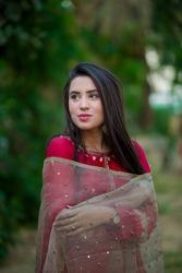Indian Pakistani desi young beautiful fashion model wearing red Kamiz Shalwar and posing with dupatta on a lush green garden background