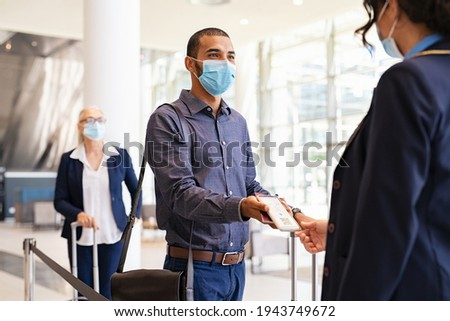 Indian passenger wearing protective face mask showing e-ticket to flight attendant at boarding gate. Mixed race businessman showing boarding pass on mobile phone to air hostess during covid pandemic. Stockfoto ©