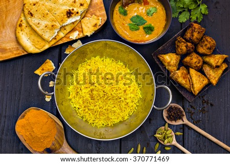 Indian pilau rice in balti dish served with chicken tikka masala curry, plain naan bread, vegetable samosas, and onion bhajis #370771469