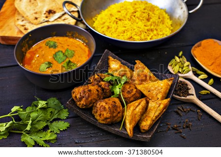 Indian pilau rice in balti dish served with chicken tikka masala curry, plain naan bread, vegetable samosas, and onion bhajis #371380504