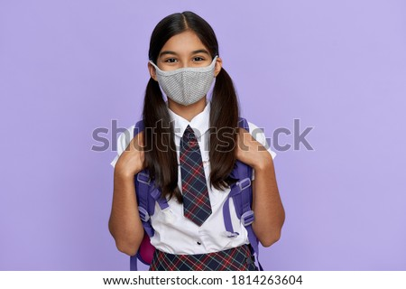 Indian preteen girl, latin kid schoolgirl student wears uniform and face mask for coronavirus protection safety holding backpack stands isolated on lilac violet background looking at camera, portrait.