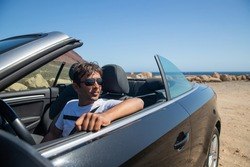 Indian rich man sitting in his convertible car wears sunglasses and looks to the side. Realized man sitting in an expensive car. Forty year old person of indian ethnicity