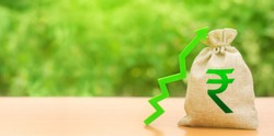 Indian rupee money bag and a green arrow up. Stability, prosperity. Strengthening of national currency, revaluation, investment attractiveness. Economic growth. Deposit interest rate rise, cheap loans