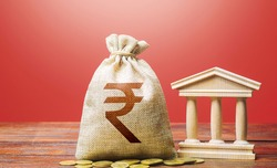 Indian rupee money bag and bank  government building. Tax collection and budgeting. GDP and GNP. Monetary policy. Support businesses in times of crisis. Lending loans, deposits. State debt.