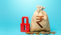 Indian rupee money bag and red padlock. Blocking bank accounts and seizing assets. Freezing of pension savings. Cash flow monitoring. Tight government control over the financial system.