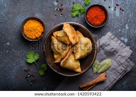 Indian samosas - fried/baked pastry with savoury filling, popular Indian snacks, served in bowl with spices and fresh cilantro on rustic background, top view. Overhead of samosas