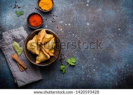 Indian samosas - fried/baked pastry with savoury filling, popular Indian snacks, served in bowl with spices and fresh cilantro on rustic background, top view. Overhead of samosas with copy space