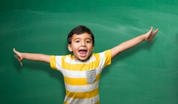 Indian school kid in hand stretched pose over green chalkboard or chalk board background, indian boy standing over green background in school