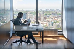 Indian serious investment banker financial analyst sitting at desk with papers working with big data, stock exchange trading operations using laptop near panoramic window in modern corporate office.