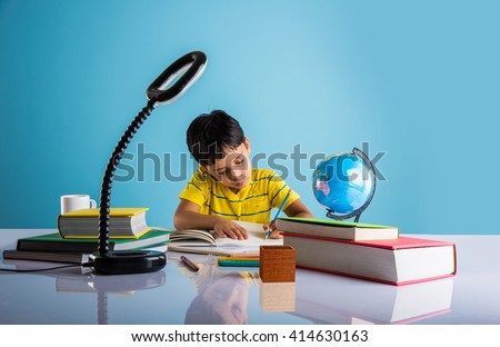 indian small boy studying or doing home work, asian boy studying with coffee mug, globe model and books on table