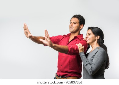 stock photo of Indian smart and cheerful / happy couple indoor, husband composing frame in the newly purchased or rented house and wife accompanying, indian couple and real estate concept