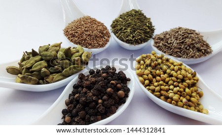 indian spices carom seeds ,fennel seeds,cumin seeds, coriander seeds,papper, cardamom isolated on white background
