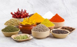 Indian Spices Collection Also Called Chili Powder, Turmeric Powder, Coriander, Fenugreek, Cumin, Mustard Seed, Salt, Black Pepper, Cardamom, Cloves, Turmeric Stick, Dry Chili on Vintage Background