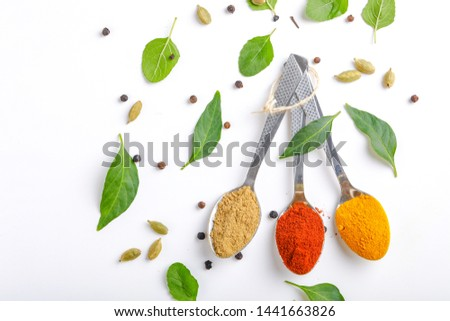 Indian Spices Red Chilli Powder, Turmeric Powder, Coriander Powder, in Spoons on White Background