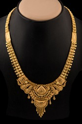 Indian style beautiful gold neckless isolated on black background.