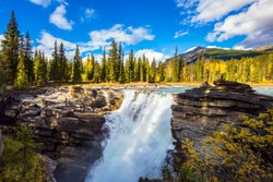 Indian summer in the Rocky Mountains, The magnificent powerful Athabasca Falls, popular with tourists. Canada. Travel and photo tourism concept