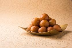 indian sweet gulab jamun in square shape brass plate, closeup view