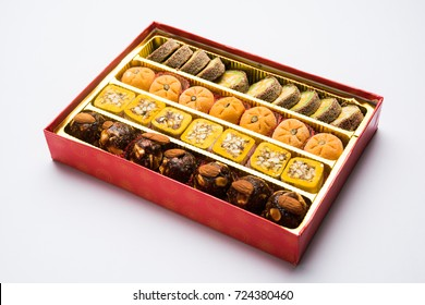 stock photo of Indian sweet or mithai in box and oil lamps or diya with flowers on decorative or colourful background, selective focus
