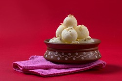 Indian Sweet or Dessert - Rasgulla, Famous Bengali sweet in clay bowl with napkin on Red Background