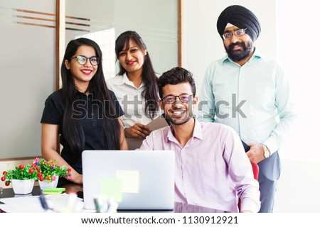 Indian team of four people posing in office with laptop