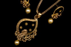 Indian Traditional fancy Jewellery Necklace or pendant with earrings on dark background.