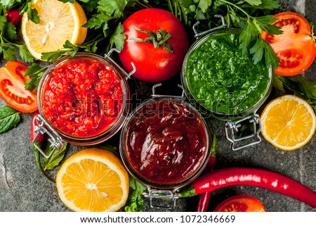 Indian traditional food, Set of three chutney for Chaat and Sev Puri - sweet date-tamarind, cilantro-mint green and red chilli garlic, On dark stone background, close top view