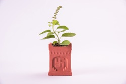Indian traditional Pot or special masonry structure known as Tulsi Vrindavan or Vrundavan with swastik and aum writting, holy hindu object, isolated, selective focus