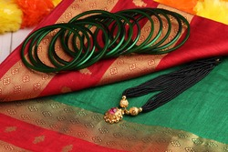 Indian traditional saree with green bangles and mangalsutra.