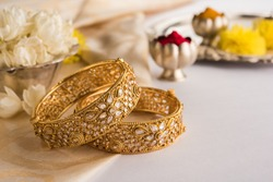 Indian traditional wedding jewellery, bangles with huldi kumkum and white flowers. selective focus