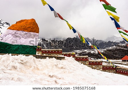 indian tricolor stone with holy buddhist flag at war memorial and snow cap mountains in background image is taken at jaswant singh war memorial bumla pass arunachal pradesh india.