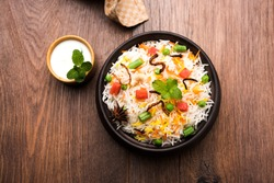 Indian Vegetable Pulav or Biryani made using Basmati Rice, served in a wooden bowl with yogurt. selective focus