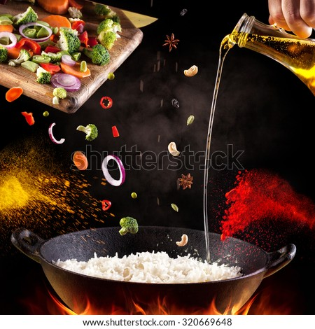 Indian vegetarian biryani with vegetables and spices in cooking process on black background
