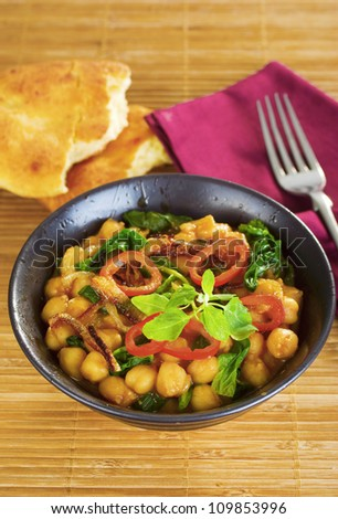 Indian vegetarian curry, with chickpeas, or garbanzo beans, with spinach, capsicums and crisply fried onions.