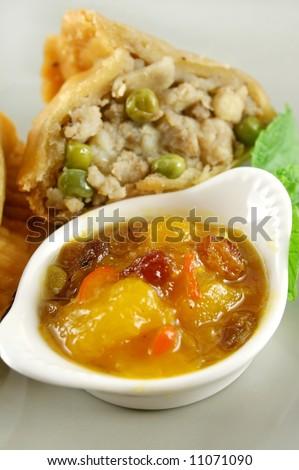 Indian vegetarian samosa with mango chutney.